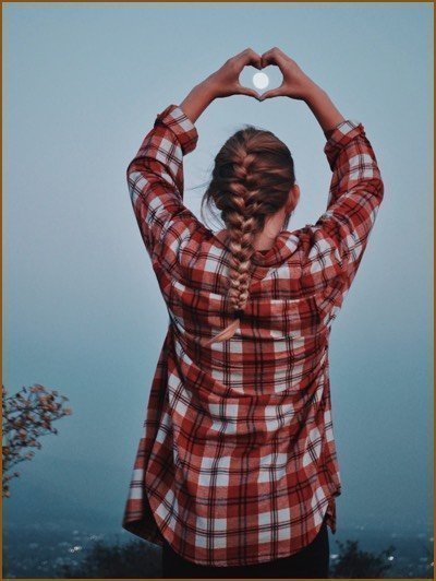 Girl making a heart sign with two hands with the full moon in the middle of her hand heart