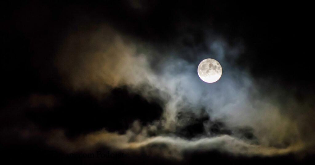 The moon breaking through the night sky clouds.