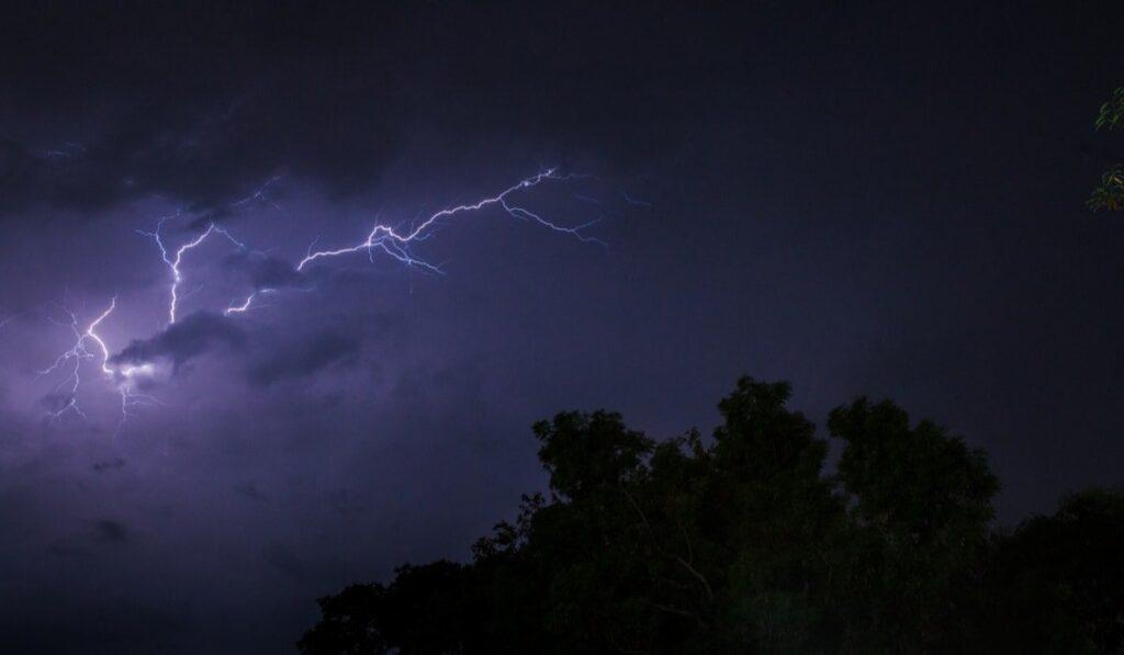 Lightening flashing at night over trees